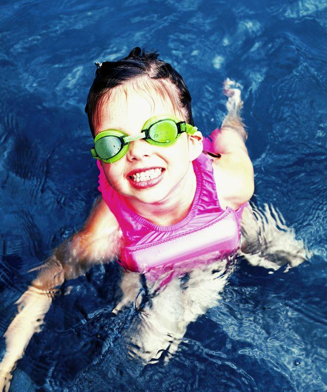 Kid in pool swim lessons